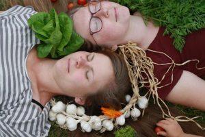 Två personer omgivna av grönsaker